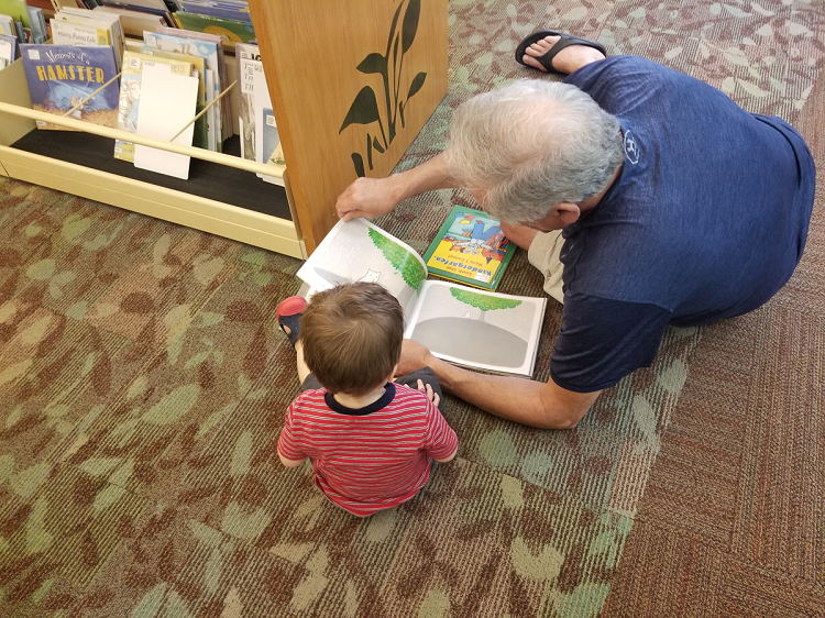 A grown-up reads to a young child sitting on the floor of the library.