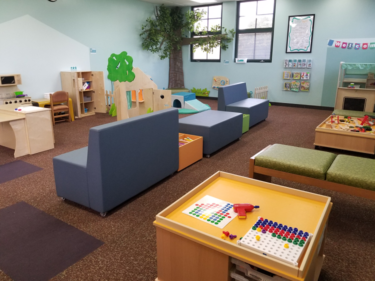 A play area featuring a play kitchen, store, train table, and construction table, as well as comfortable seating for adults (soft benches).