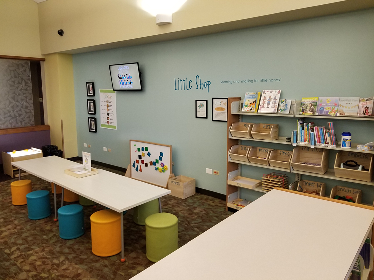 An arts and crafts area featuring two long tables and stools. There is also a magnet board and light table, as well as shelves with supplies.