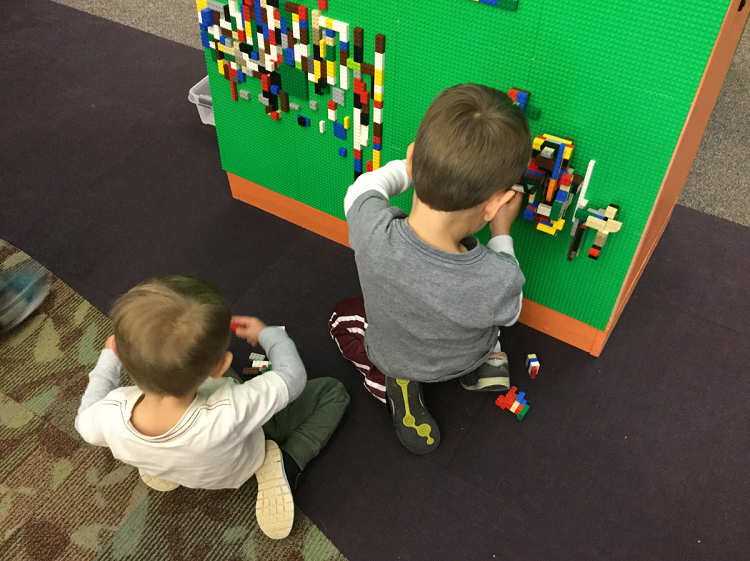 Two young children play at a LEGO building wall.
