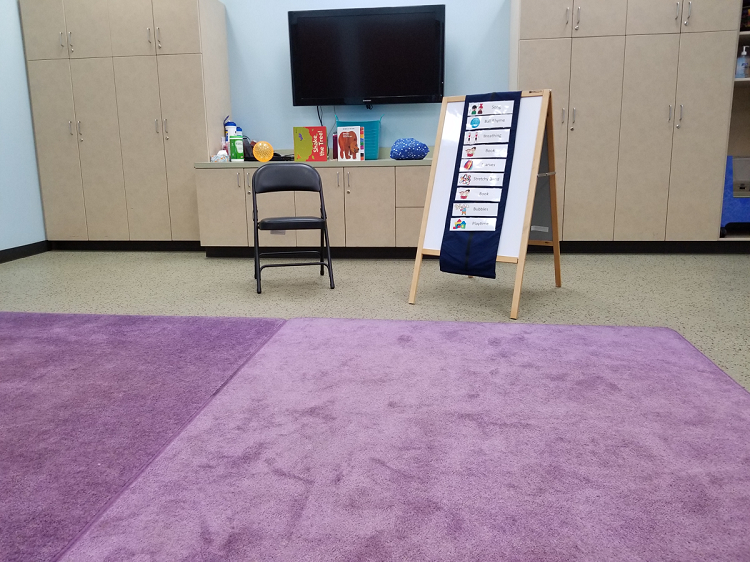 Our programming room is set-up for sensory storytime with two purple rugs, a chair, a visual schedule, and books and toys behind the chair on a cabinet.