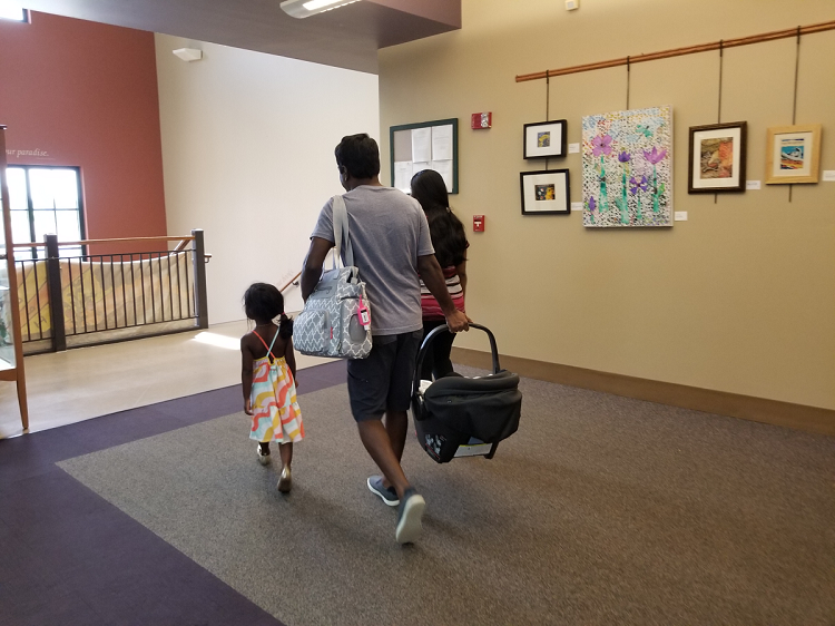 A family of four leaving the Kids and Teens department, heading towards the stairs.