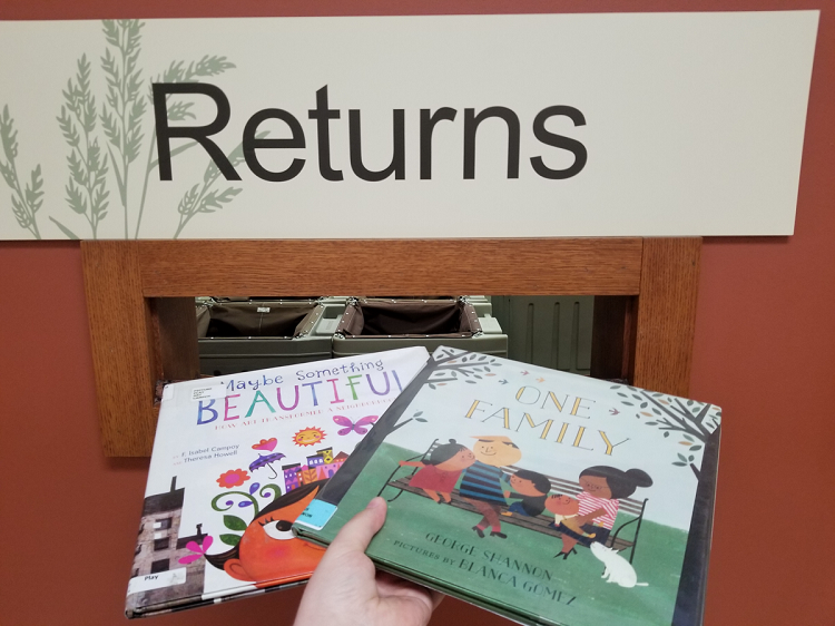 "Two picture books are being placed through a slot in the wall. Above the slot, a sign reads ""Returns""."