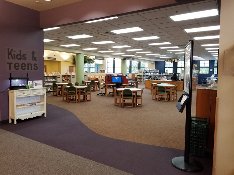A large open space with table, chairs, computers, and a large desk. On the left, Kids & Teens is painted on the wall.