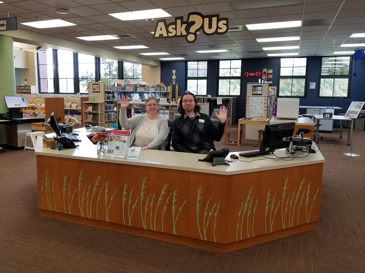 Two librarians sit and wave hello at a desk. Over the desk, a hanging sign reads Ask Us.