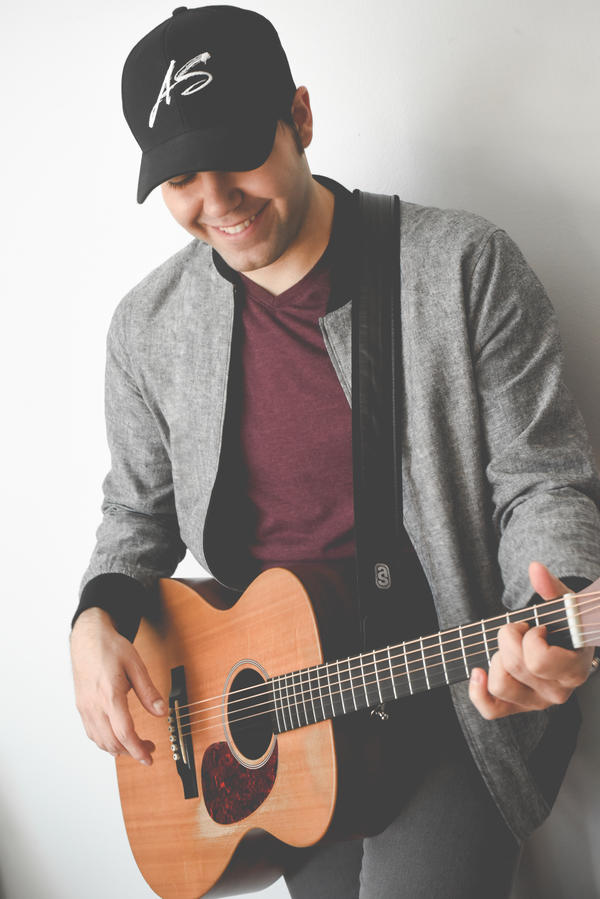 A photo of Andrew Salgado smiling and playing guitar.