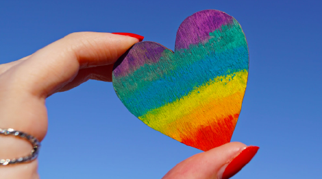 A hand with red fingernails holding up a small, rainbow-colored heart against a blue sky.